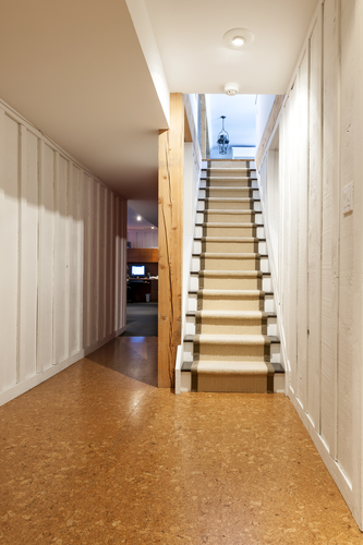 Like most parts of your home, your stairs will gradually wear out with time. Sometimes they may require a total replacement, but more often than not, they will merely need to be refinished. As they are sitting in your basement area, they are more susceptible to moisture than the rest of your house, so that rot can set in. It is important that you decide if they do need replacing, as there will be added expense if you refinish them, only to find out several months later you should have replaced them in the first instance. If you do choose to refinish your basement steps, then read our guide on the best options available to you. Painting And Staining If you have just renovated your basement or are merely looking to refinish your stairs, you should note that some homeowners don't like to cover their stairs up, preferring their natural look. If this is you, then you might think about painting or staining them. Not only is this extremely affordable, but it also can look superb if done correctly. If you choose to stain them, then make sure that you have sanded them down properly, so that when you stain them the results will look good and the effect will last for a while. If you feel that painting your steps is the better-looking option for your home, then make sure that you use a latex floor paint. This style of paint is very durable and will last for a considerable amount of time, but of course, it will wear down eventually. You merely top it up with another lick of paint to make it look good again. One more benefit over stain is that there are plenty of colors available if you are painting, while stain only has so many. Of course, if you paint over the wooden stairs you will lose the sight of the natural grain in the wood. If you want to retain the natural look, then stain is the way to go. Carpet Many homeowners like the look and feel of carpet on their stairs. It not only makes them look new, but it also makes the stairs far easier to walk on. However, with the problem of damp and moisture in certain basements, you will find that carpet will retain any moisture and become moldy. You don't really want your pristine cream-colored carpet spotted with mold, so really think this option through. Carpet Runner Instead of going the whole hog and laying down a mass of carpet, a carpet runner may solve your refinishing issue. Carpet runner is merely a thinner carpet that is stapled in place. This can be a viable cheaper option to full carpeted stairs, and when coupled with the rest of the step being stained in varnish, they can look good. Vinyl Some homeowners are now using vinyl to refinish their staircases, and this is a good option as it is resilient to damp and mold while being easy to clean. Vinyl flooring merely requires metal strips to hold it down and is easy to replace. It is also a cheaper option that full carpeting or expensive varnishing and staining. If you decide that none of these options are viable due to rot and dampness, you should look at replacing your basement stairs.
